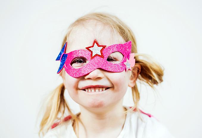 Vaalea tyttö virnistää kameralle kimaltava ja pinkki naamio kasvoillaan.