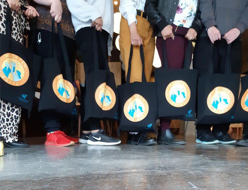 Rivissä seisoo joukko ihmisiä, joilla kaikilal on käsissään Nuorten päivä -kangaskassit. Vain henkilöiden jalat näkyvät.